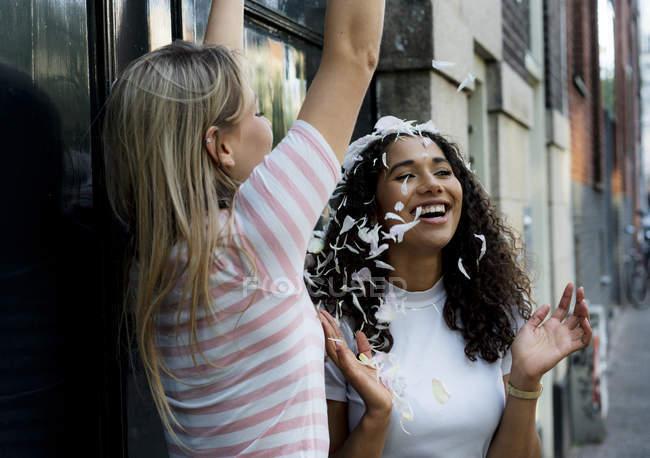 Две счастливые девушки бросают лепестки — стоковое фото