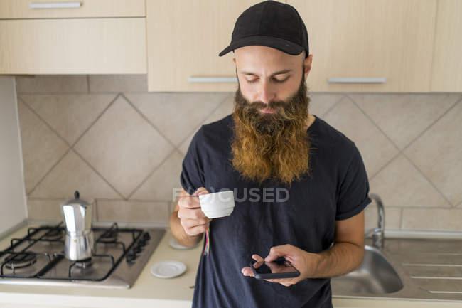 Бородатый мужчина стоит на кухне с чашкой эспрессо и смотрит на сотовый телефон. — стоковое фото
