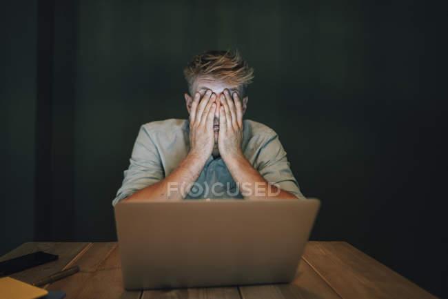 Homem tired que senta-se no escritório, trabalhando tarde na companhia startup, cobrindo os olhos — Fotografia de Stock