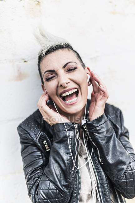 Exuberant punk woman listening to music with earbuds — Stock Photo