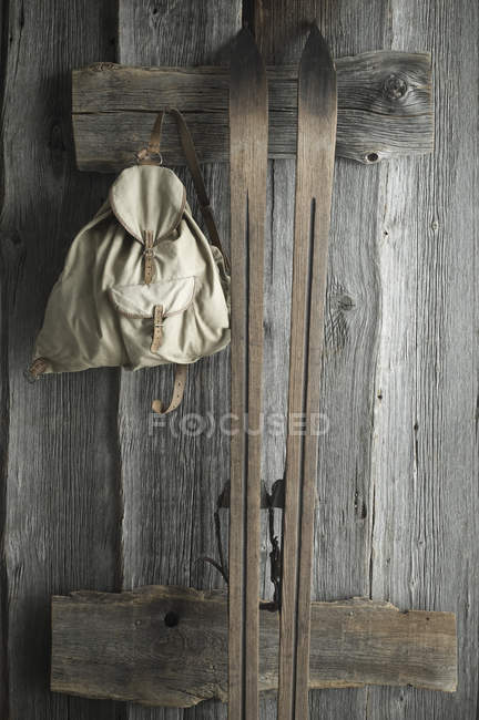 Wooden ski and old backpack on a rustic wooden wall — Stock Photo