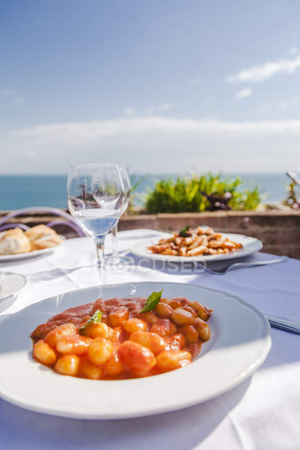 Italy, Atrani, plate of gnocchi with tomato sauce — Stock Photo