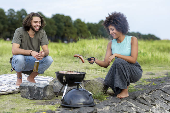Happy couple having a barbecue in nature — Stock Photo