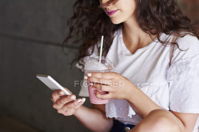 Woman's hands holding smartphone and plactic cup of smoothie — Stock Photo
