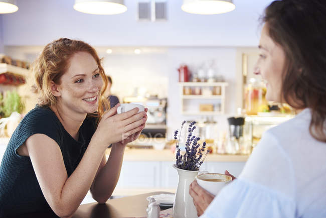Two women talking and drinking coffee at cafe — Stock Photo