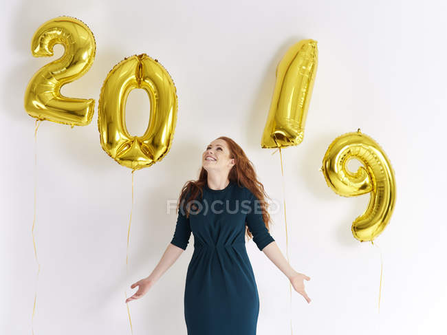 Happy young woman with golden balloons forming date 2019 — Stock Photo