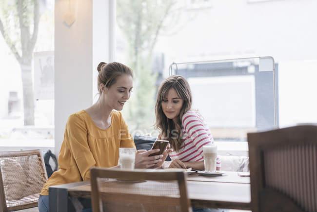 Zwei Freundinnen treffen sich in einem Coffeeshop mit dem Smartphone — Stockfoto