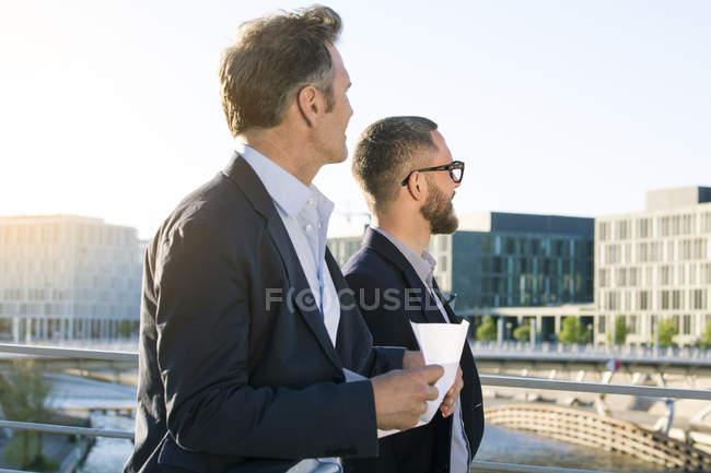 Deux hommes d'affaires sur un pont dans la ville regardant autour — Photo de stock
