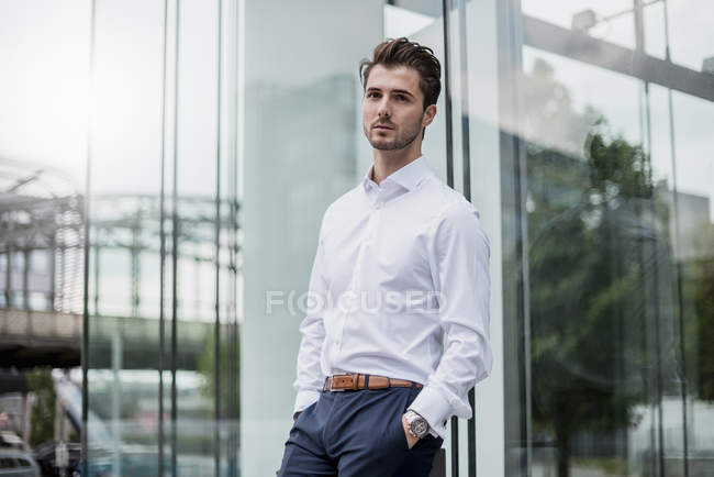 Businessman leaning against glass facade — Stock Photo