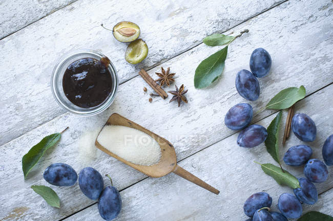 Frasco de preservação do atolamento e de ingredientes da ameixa na madeira — Fotografia de Stock