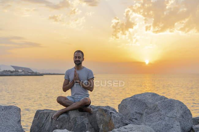 В Испании. Человек медитирует во время восхода солнца на скалистом пляже — стоковое фото