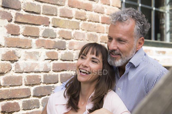 Доросла пара сидить на сходах і сміється. — стокове фото