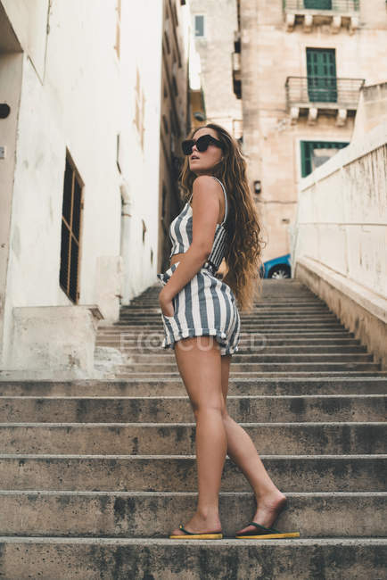 Teenage girl wearing striped beach wear, posing on stairs — Stock Photo