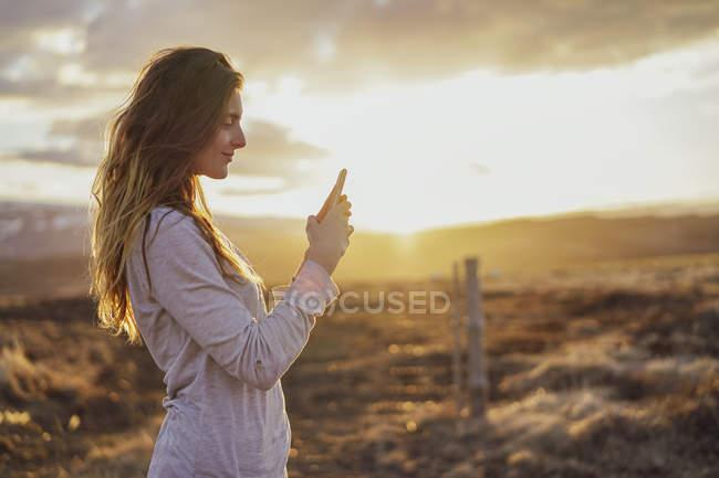 Islândia, jovem mulher usando smartphone ao pôr do sol — Fotografia de Stock