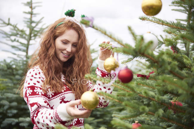 Portrait of redheaded young woman decorating Christmas tree outdoors — Stock Photo