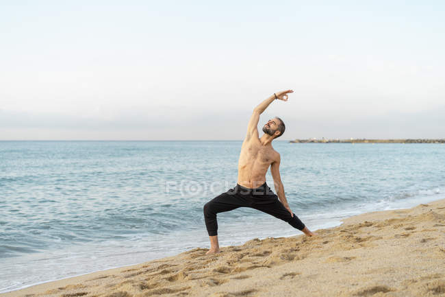 Spain. Man doing yoga on the beach in the evening — Stock Photo
