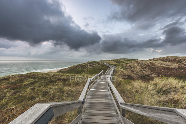 Germany, Schleswig-Holstein, Sylt, Wenningstedt, boardwalk to the beach — Stock Photo
