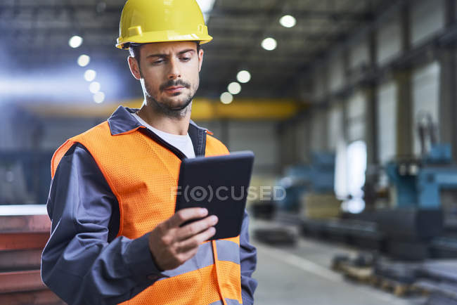 Confident man using tablet in factory — Stock Photo