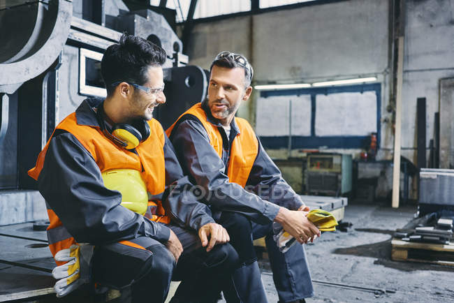 Men wearing protective workwear talking during break in factory — Stock Photo