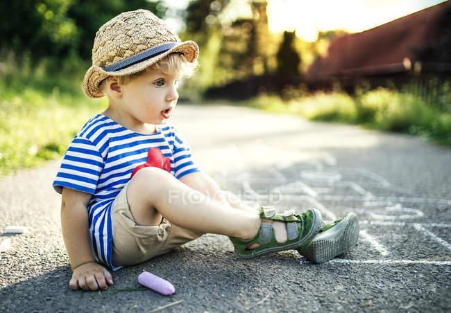 Petit garçon rêveur assis dans la rue — Photo de stock