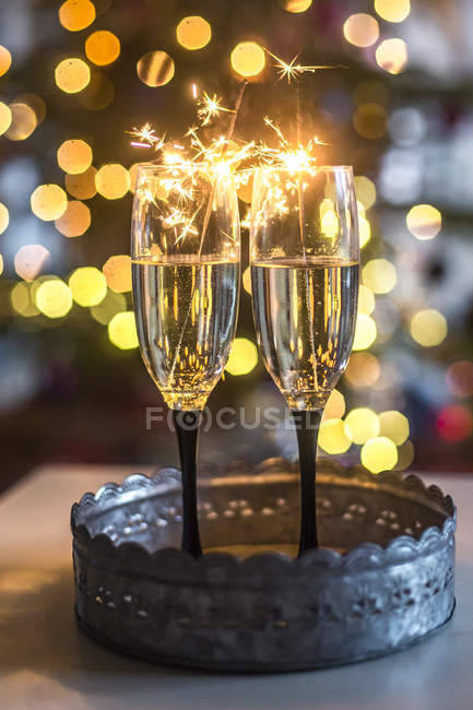 Two champagne glasses and sparklers in front of Bokeh — Stock Photo
