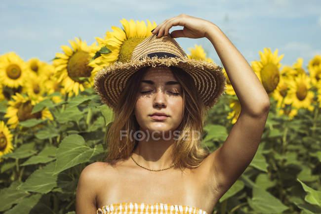 Портрет молодої жінки з солом'яним капелюхом в області соняшнику — стокове фото