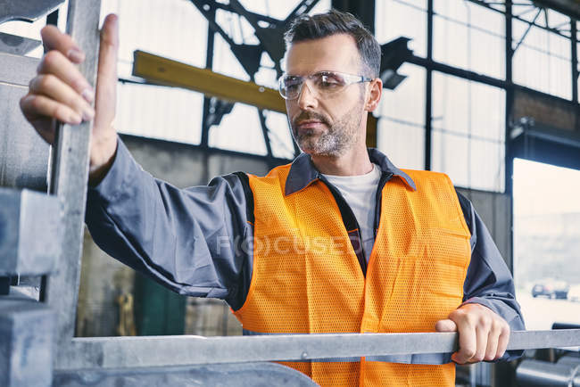 Man wearing protective workwear working in factory — Stock Photo