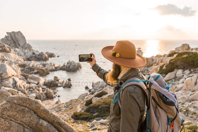 Italy, Sardinia, hiker with hat and backpack taking photo of the sea with cell phone — Stock Photo