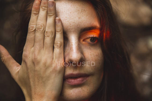 Portrait of young woman with freckles covering eye — Stock Photo