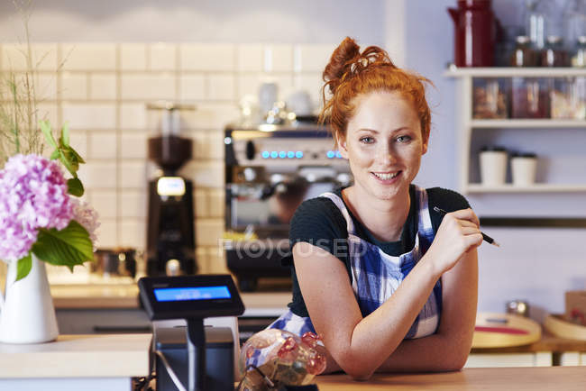 Portrait of smiling young woman at the counter in a cafe — Stock Photo
