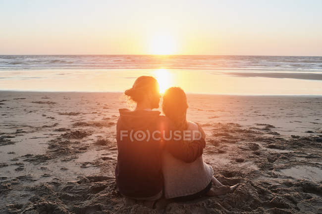 Portugal, Algarve, romantic couple sitting on beach at sunset — Stock Photo