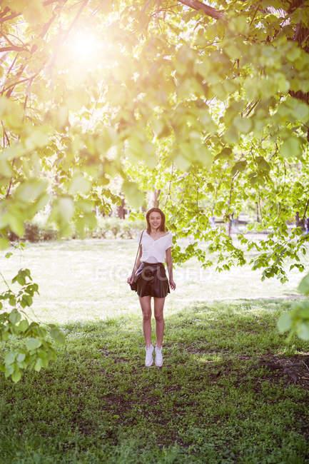 Lächelnde junge Frau steht im Park — Stockfoto