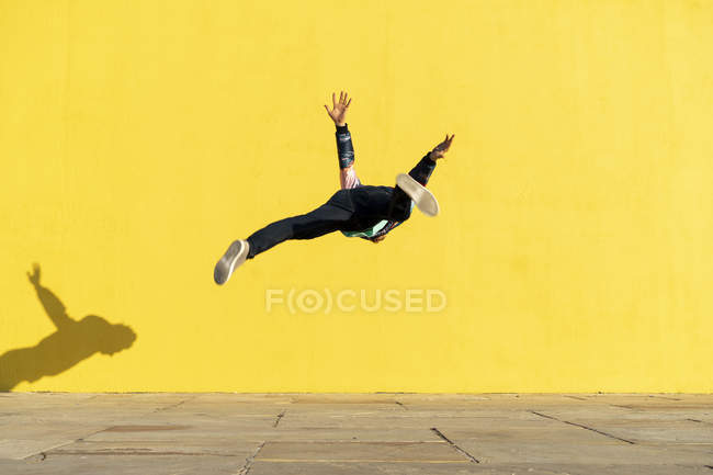 Acrobat jumping somersaults in front of yellow wall — Stock Photo