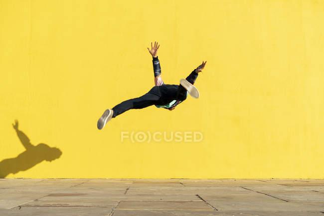 Акробат прыгает сальто перед желтой стеной — стоковое фото