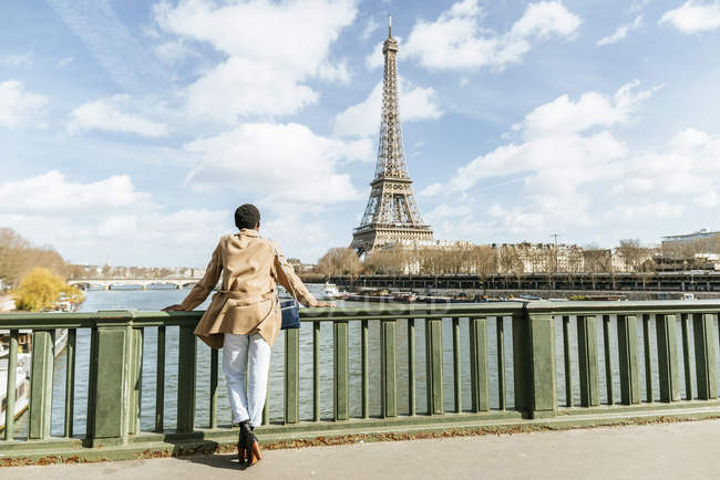 France, Paris, Female tourist looking at Eiffel tower and the Seine river — Stock Photo