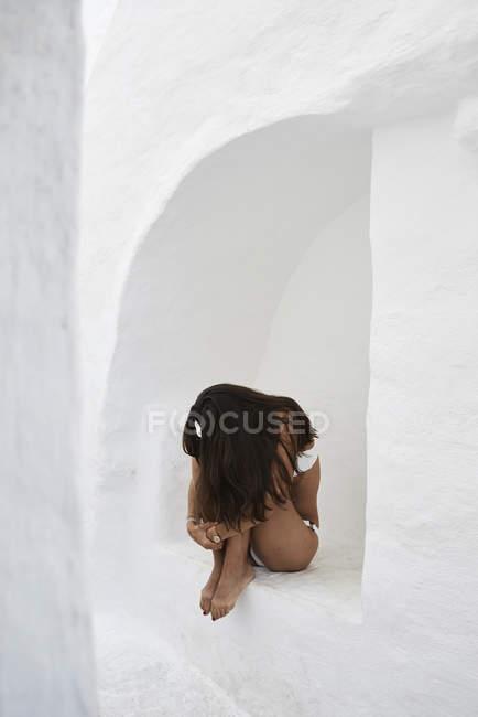 Giovane donna accovacciata in nicchia muro — Foto stock