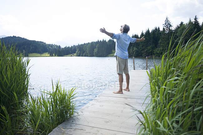 Німеччина, Mittenwald, літня людина, що стоїть з витягнутих рук на пристані на озері — стокове фото