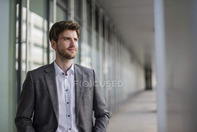 Uomo d'affari fiducioso in città guardando lateralmente — Foto stock