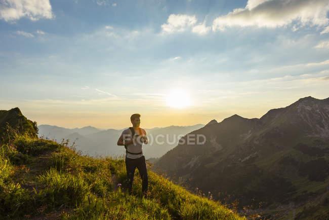 Hombre senderismo en las montañas al atardecer - foto de stock