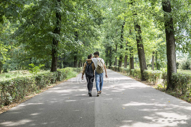 Back view of young gay couple with backpacks walking hand in hand on path — Stock Photo