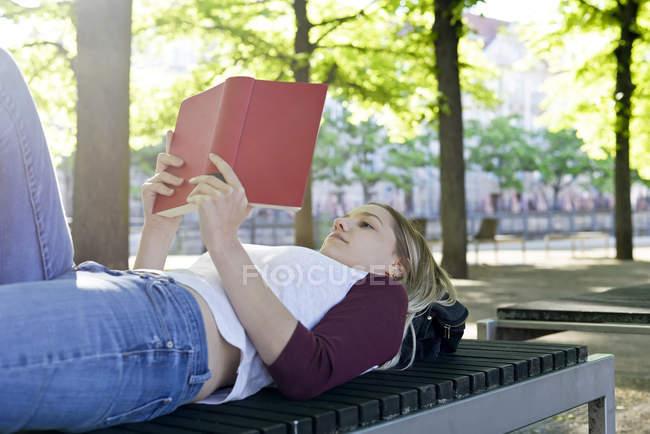Молода жінка читає книгу на лавці — стокове фото