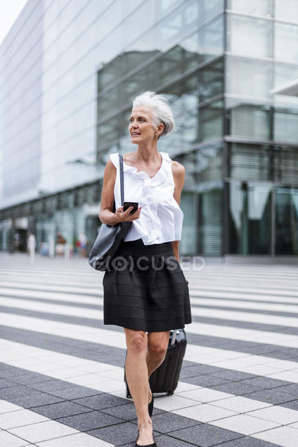 Senior woman with cell phone and baggage on the move in city — Stock Photo