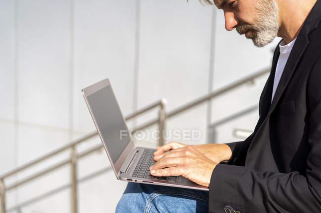 Бізнесмен, сидячи на відкритому повітрі, використовуючи ноутбук — стокове фото