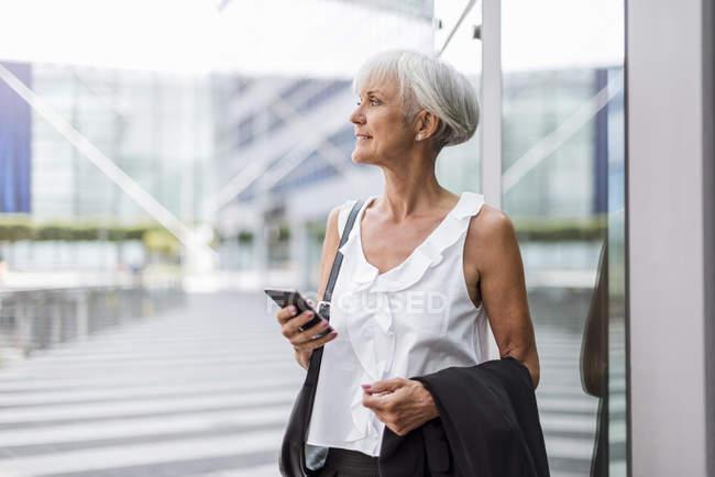 Seniorin schaut sich mit Handy in der Stadt um — Stockfoto