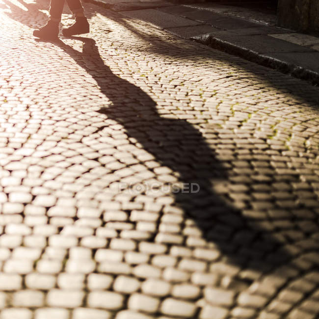 Shadow of woman crossing sunny street — Stock Photo