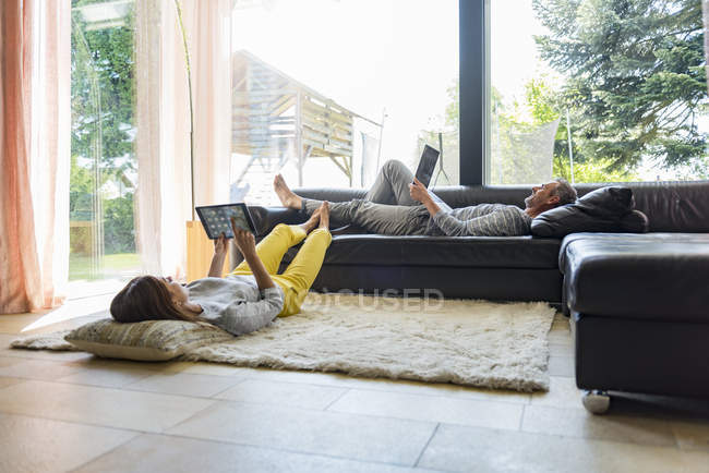Couple relaxing in living room at home using tablet and laptop — Stock Photo
