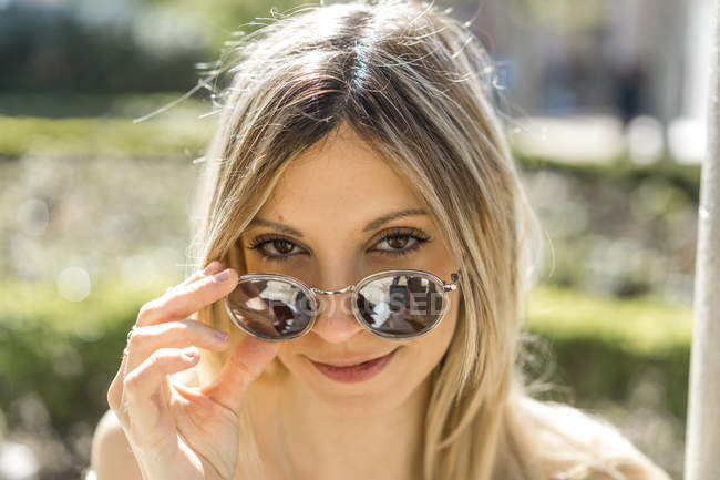 Portrait of smiling young woman with mirrored sunglasses — Stock Photo