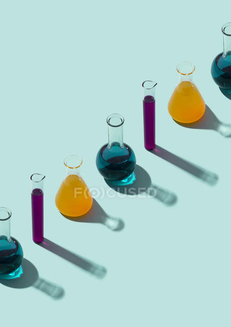 Fila de tubos de ensayo con fondo líquido y cian - foto de stock