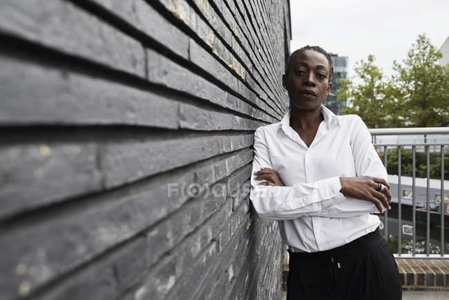 Портрет серьезной деловой женщины, прислонившейся к стене — стоковое фото