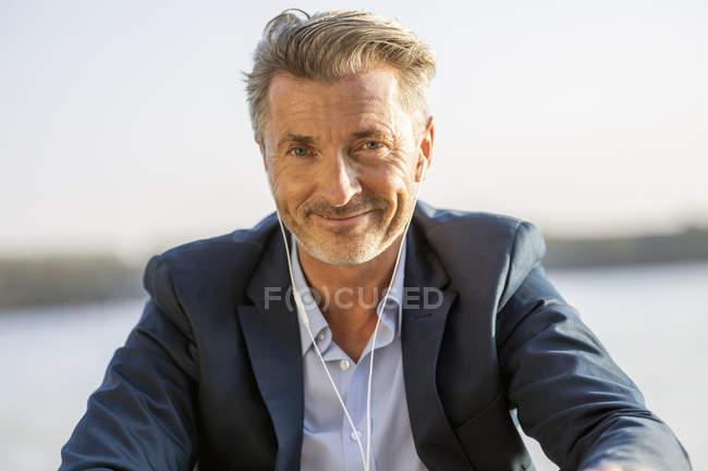 Retrato de homem de negócios sorridente com fones de ouvido sentado no lago — Fotografia de Stock